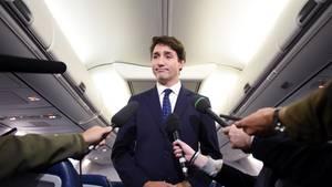 Ein Mann im Anzug steht im Mittelgang eine Flugzeuges und spricht in vier Mikrofone, die ihm Reporter hinhalten