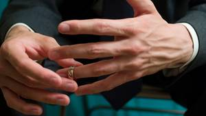 Ein Mann nimmt sich den Ehering vom Finger