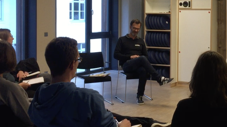 In einem Seminarraum sitzt sin Mann mit übergschlagenen Beinen auf einem Stuhl, vier Zuhörer ihm gegenüber im Halbkreis