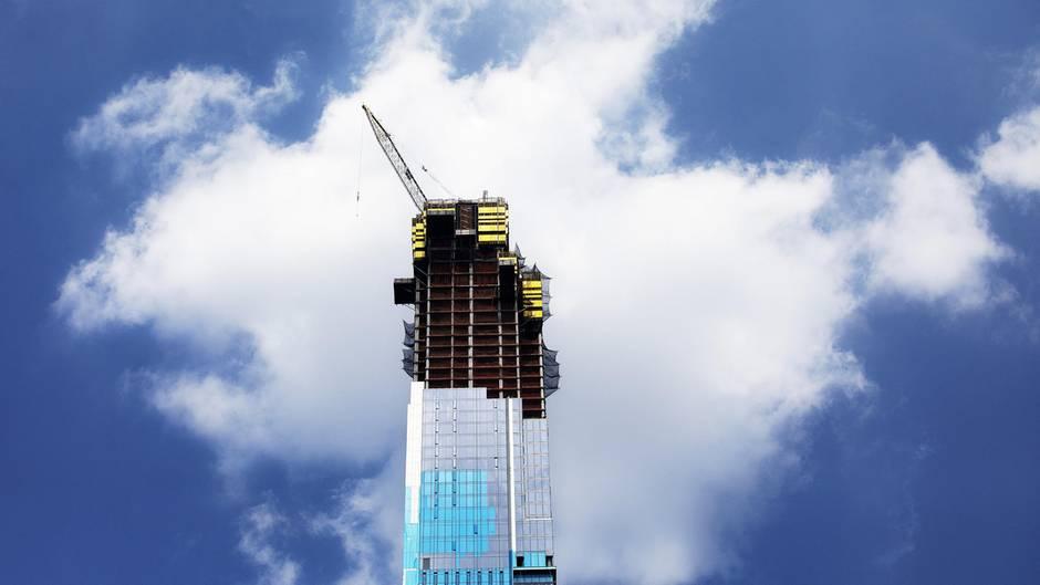 Auf der Spitze eines schlanken Wolkenkratzers im Bau steht ein Kran, hinter dem eine Wolke im Himmel hängt