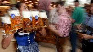 Eine Bedienung trägt volle Maßkrüge mit Bier auf dem Oktoberfest