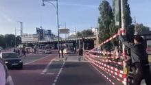 """Aktivisten von """"Extinction Rebellion"""" spannen Flatterband zwischen Ampeln in Berlin und sperren so eine Straße am Alexanderplatz"""