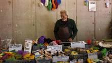 Auf einem Tisch vietet ein alter Mann waren an, die in der DDR produziert worden sind