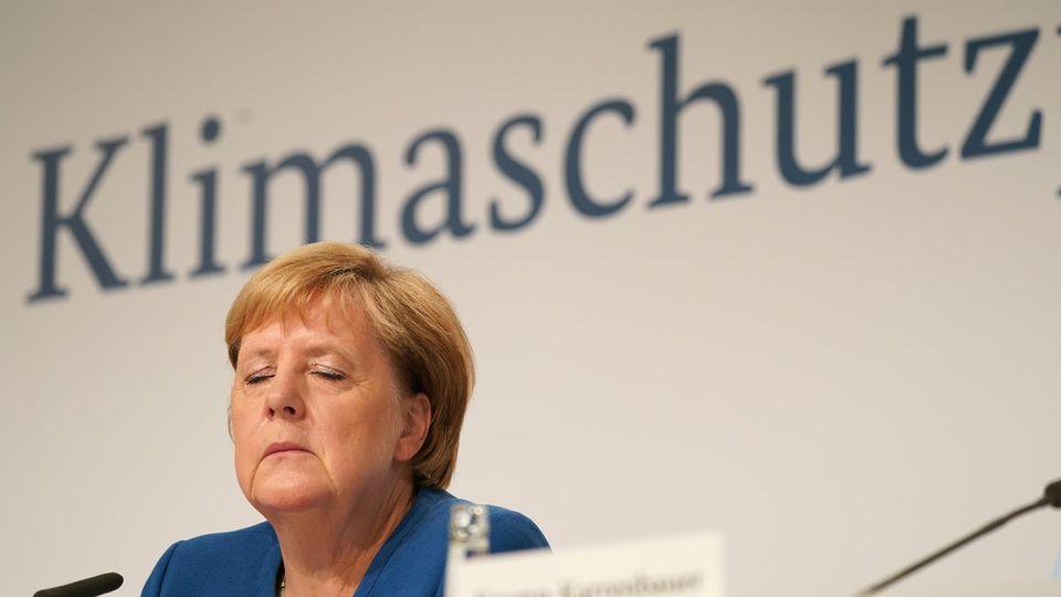 """Bundeskanzlerin Angela Merkel sitzt im blauen Blazer und mit geschlossenen Augen auf einem Podium unter dem Wort """"Klimaschutz"""""""