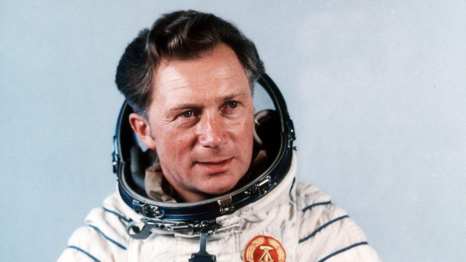 Ein Mann mit Seitenscheitel posiert in einem Weltraumanzug mit DDR-Wappen für ein Foto