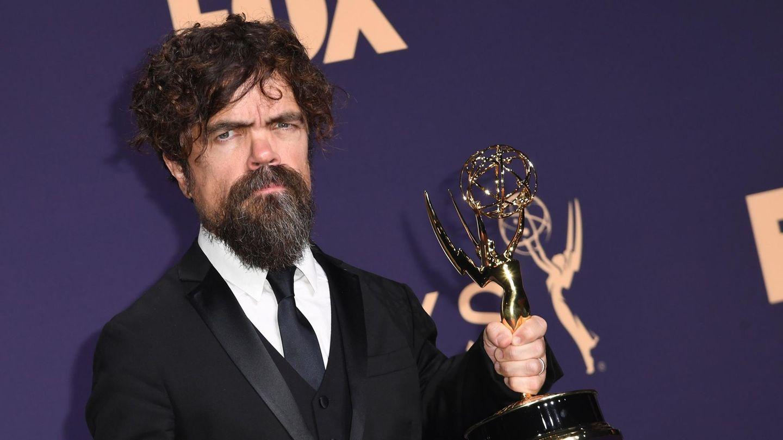 Ein kleinwüchsiger Mann mit dunklen Locken und Vollbart hält einen goldenen US-Fernsehpreis in der linken Hand