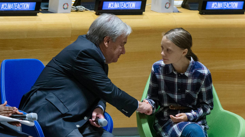 Auf einem Podium schüttelt ein grauhaariger Mann im Anzug die Hand eines Mädchens mit Zopf und Karohemd