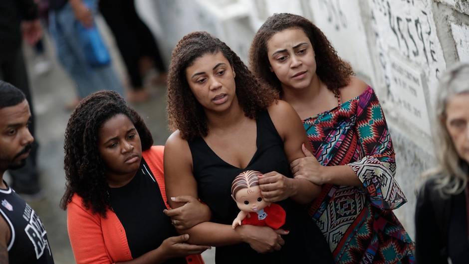 Vanessa, die Mutter der achtjährigenÁgatha (Mitte), geht hinter dem Sarg her. In der Hand hält sie eine Puppe ihrer Tochter.