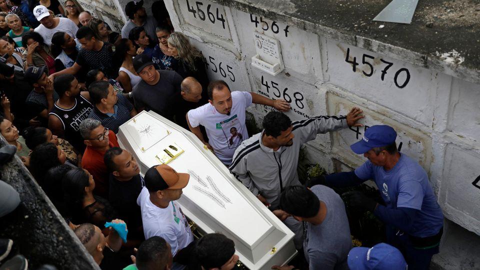 Trauergäste tragen und begleiten den Sarg mit den sterblichen Überresten der Achtjährigen Ágatha Sales Felix.