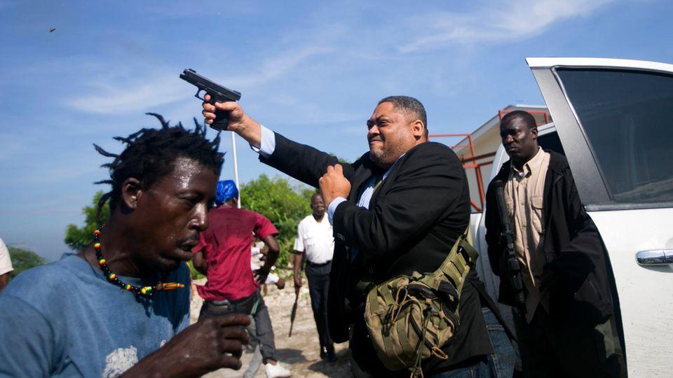 Ralph Fethiere, Senator der Opposition, feuert seine Waffe vor dem Parlament in Haiti ab