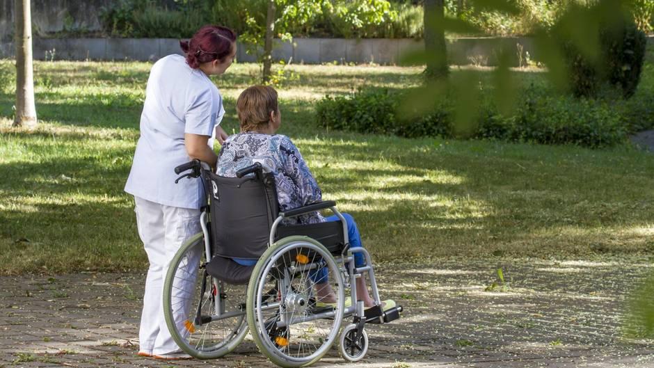 Pflegeheimbewohnerin sitzt im Rollstuhl, Pflegerin bei Spaziergang mit Frau im Rollstuhl.