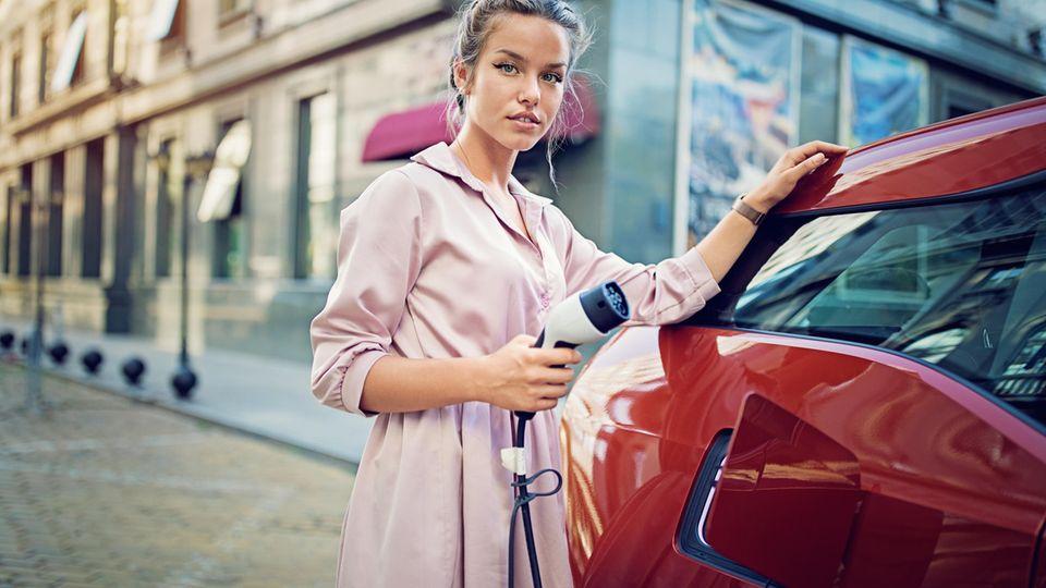 Frau lädt Elektroauto