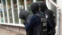 Zwie vermummte Polizisten in dunkelblauer Kampfmontur führen einen Mann ab, der sich seine Kapuze übergezogen hat