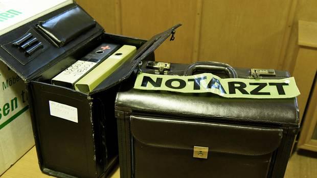 Ein Koffer mit Notarzt-Abzeichen und weitere Beweismittel stehen beim Prozessauftakt im Gerichtssaal.