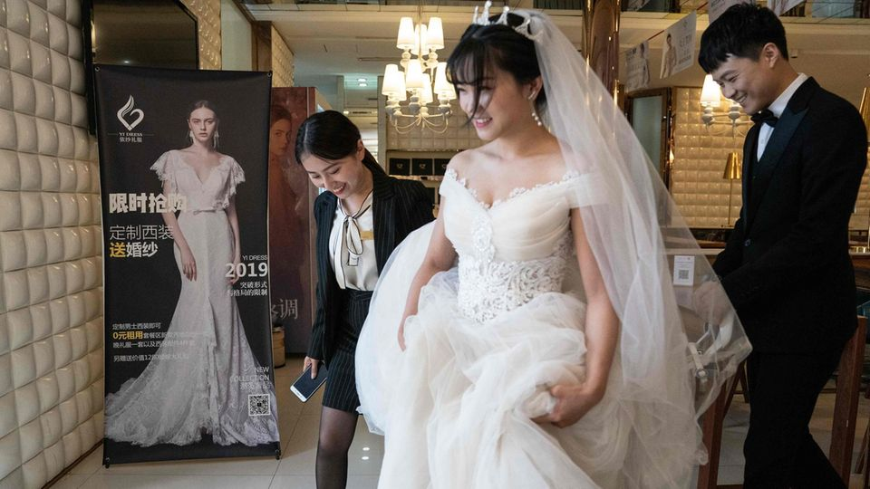Eine Chinesin in weißem Brautkleid rafft ihren Rock mit den Händen und geht vor ihrem Bräutigam im Anzug her