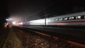 In der Dunkelheit beleuchten Helfer mit großen Scheinwerfern ICE 552 auf freier Strecke