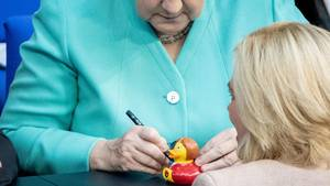 Bundeskanzlerin Angela Merkel unterschreibt eine Quietscheente