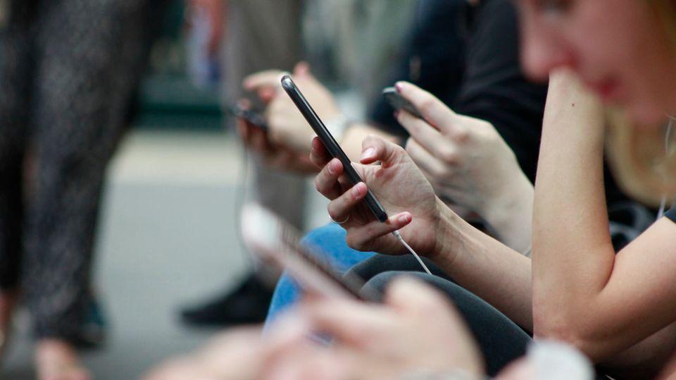 Nahaufnahme von vielen Händen, die Smartphones in der Hand halten