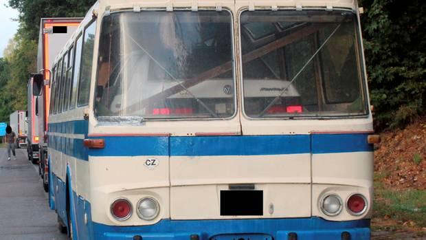Ein weißer Passat steht im Innenraum eines weiß-blauen Reisebusses aus den 70er Jahren.