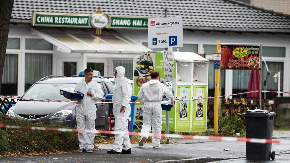 Drei Männer in weißen Overalls stehen vor einem China-Restaurant in Göttingen und sichern Spuren