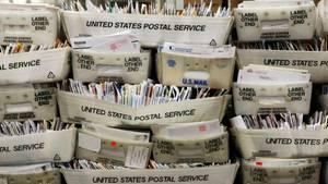 Hunderte Briefe stapeln sich in Postboxen.