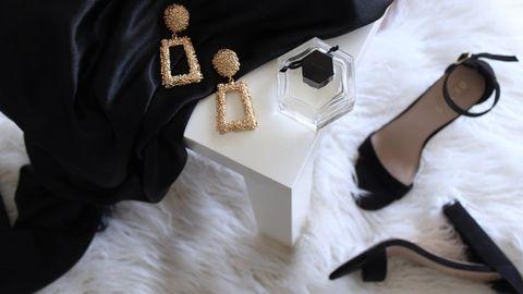 Kleid, Ohrringe und Schuhe liegen nebeneinander