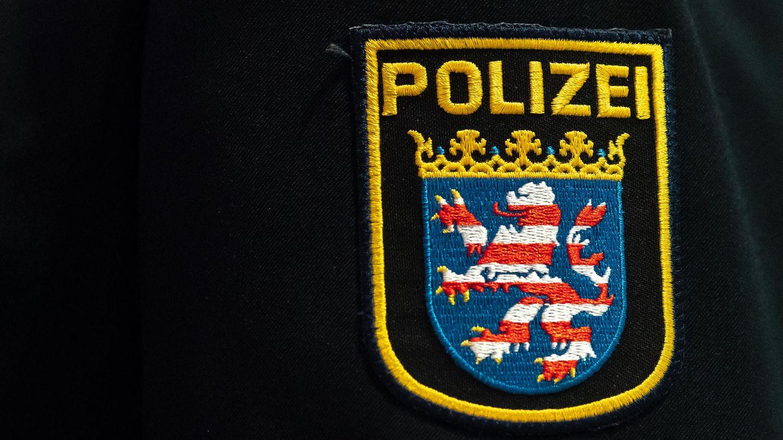 Auf dem Ärmel einer dunkelblauen Uniformjacke prangt das Wappen der Polizei Hessen