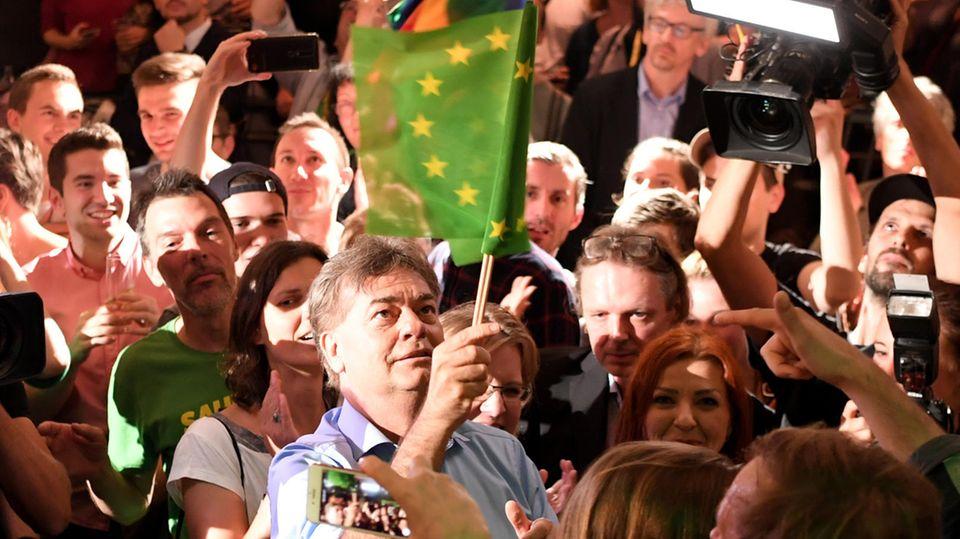 Werner Kogler schwenkt die europäische-grüne Flagge der Grünen in Österreich