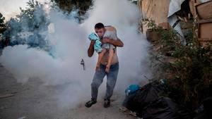 Ein Mann läuft mit einem Jungen auf der Schulter vom Flüchtlingslager Moria weg