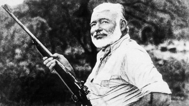 Ernest Hemingway mit Gewehr in der Hand. Neben ihm ein erlegter Jaguar liegend