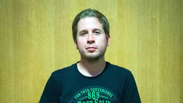 Kevin Kühnert, in T-Shirt und Jeans vor einer Holzwand