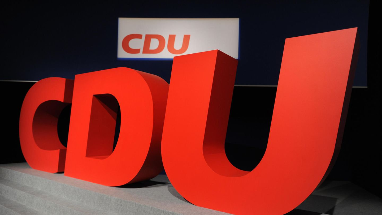 """Auf einer Bühne stehen drei rote Buchstaben """"CDU"""" in der Typographie des CDU-Logos"""