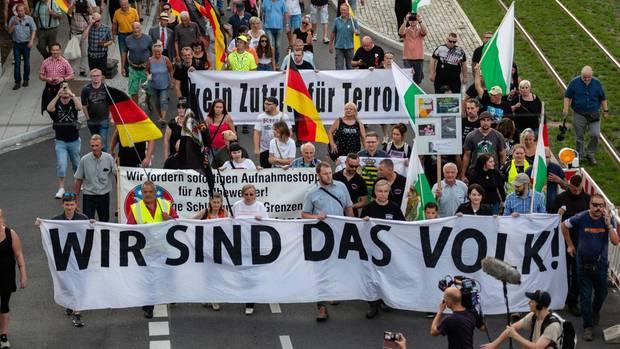"""Eine fahnenschwenkende Menge mit einem großen """"Wir sind das Volk""""-Banner"""