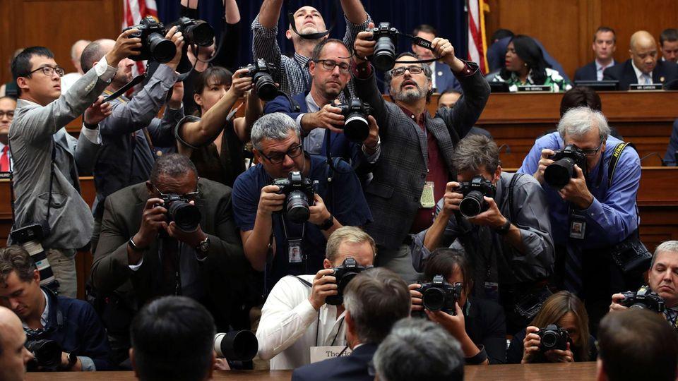 Joseph Maguire vor einer großen Gruppe von Fotografen sitzend