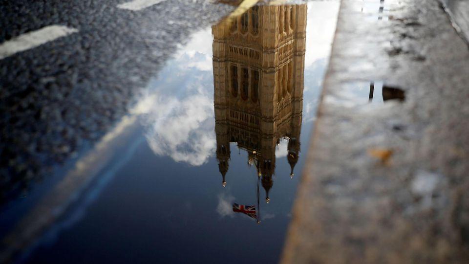 Das britische Parlament, sich kopfüber in einer Straßenpfütze spiegelnd