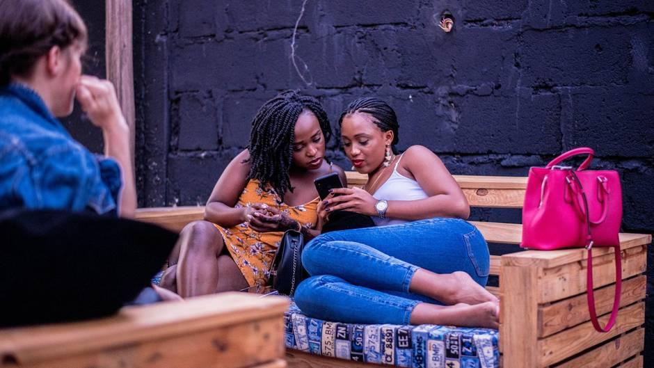 Frauen, die ihr Handy schauen während eine andere Frau sie dabei beobachtet