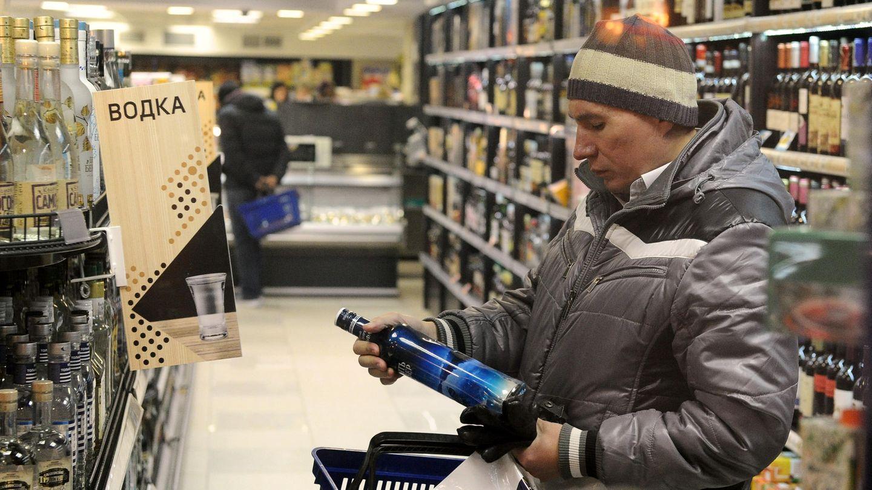 Russland, Moskau: Ein Mann legt in einem Geschäft eine Flasche Wodka in seinen Einkaufskorb