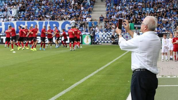 Fritz Keller am Spielfeldrand, ein Smartphone in der Hand haltend