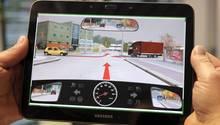 Ein Dekra-Mitarbeiter zeigt einem Prüfling eine Aufgabe aus der Führerscheinprüfung