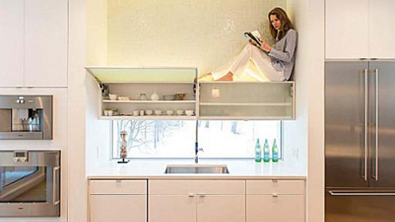 Frau sitzt auf Küchenschrank