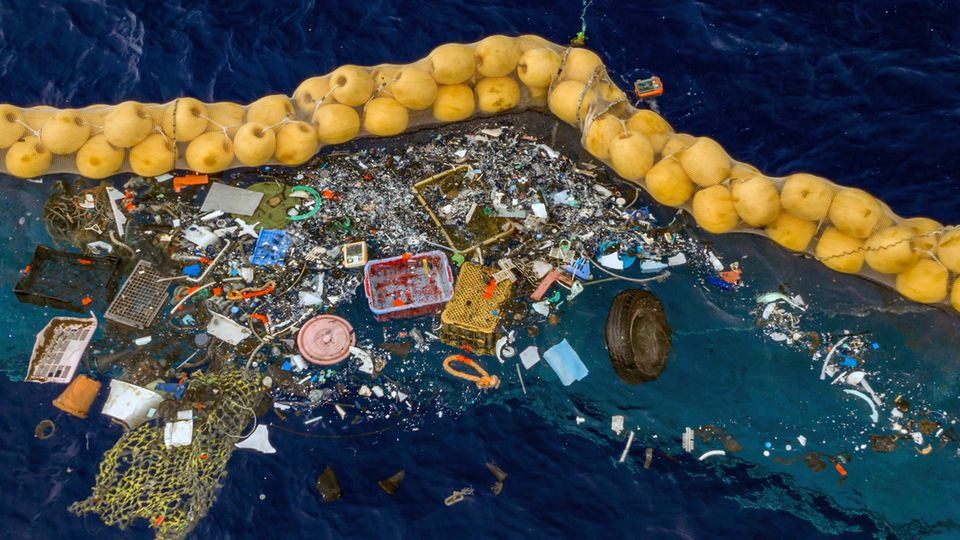 Plastikstücke schwimmen vor einer Dichtung im Meer