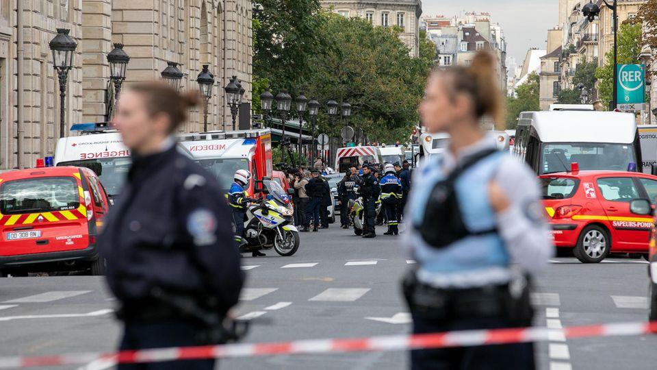 Zwei Polizistinnen stehen in Schutzwesten hinter einem Absperrband, während im Hintergrund Rettungswagen und Polizisten stehen