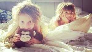 Zwei kleine Mädchen liegen im Bett