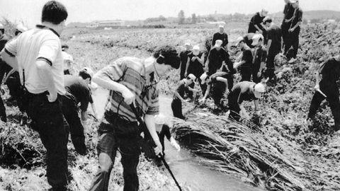 Auf einem Schwarz-weiß-Foto stehen koreanische Ermittler an einem Wassergraben und untersuchen den Tatort