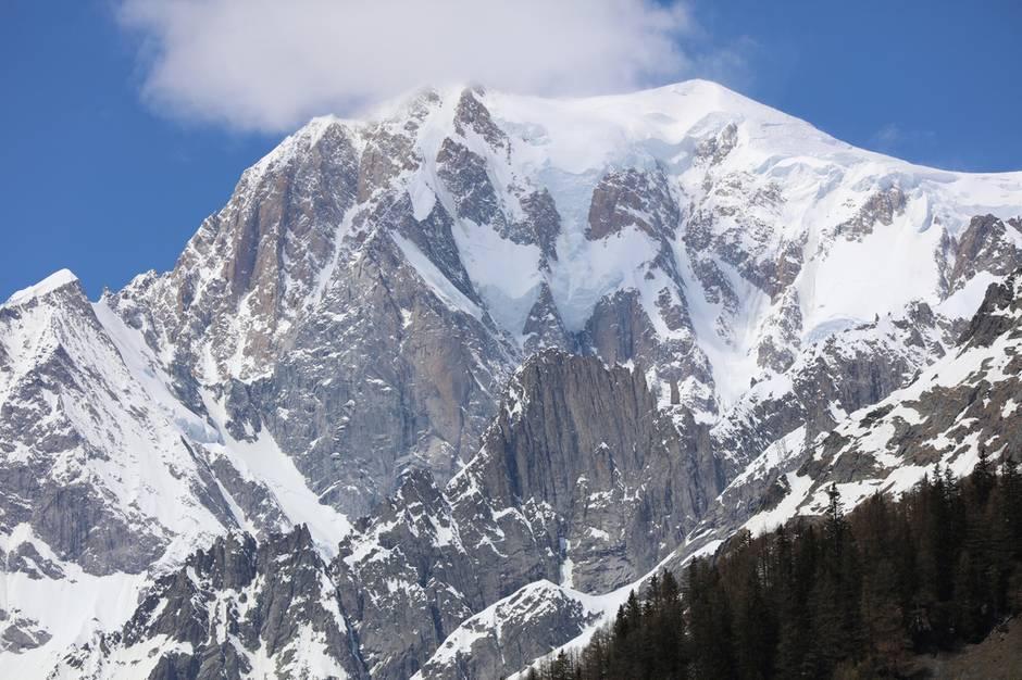 Von der italienische Seite aus gesehen: Das Gipfelmassiv des Mont Blanc mit dem Peuterey-Grat, der sich von links zum Gipfel zieht. Wegen erhöhter Steinschlagsgefahr kann diese Klettertour heute kaum noch begangen werden.