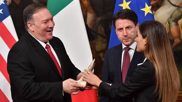 Eine italienische Fernsehreporterin überreicht US-Außenminister Mike Pompeo ein Stück Käse.