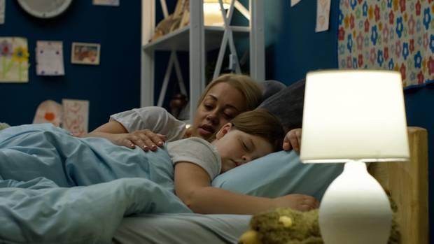 Ein Mädchen schläft im Arm ihrer Mutter