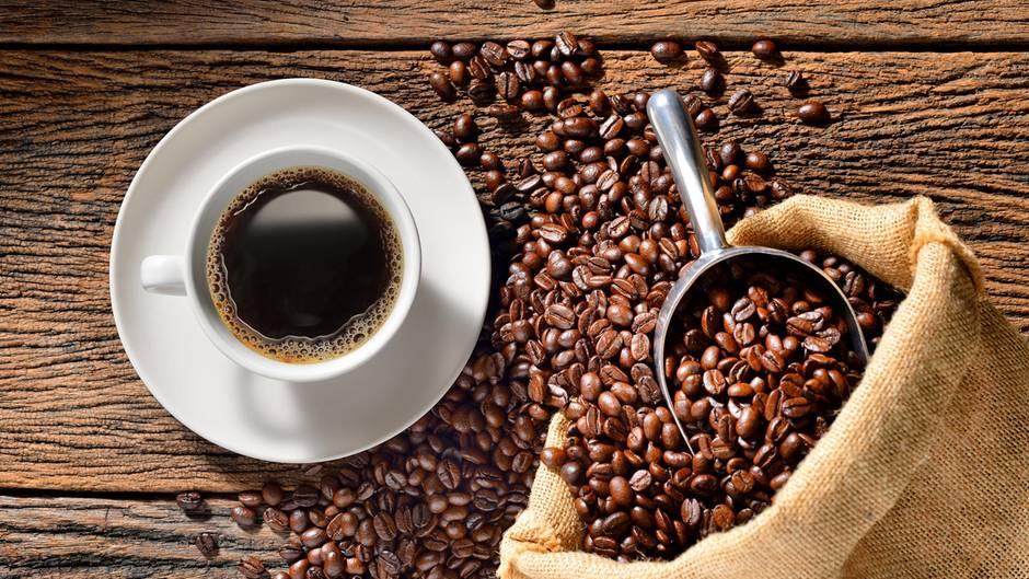 Kaffeepulver: Eine Tasse Kaffee und Kaffeebohnen auf einem Tisch