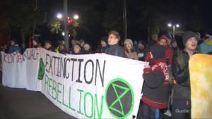 """In der Dunkelheit eines Herbstmorgens stehen Demonstranten hinter einem Banner mit dem Schriftzug """"Extinction Rebellion"""""""