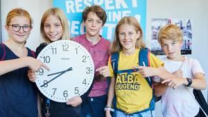 Schüler zeigen auf eine Uhr, die 8.40 Uhr zeigt